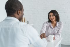 African american girlfriend and boyfriend drinking coffee and holding hands. At home stock photography