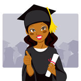 African American Graduate. Beautiful african american woman celebrating graduation day holding diploma in her hand and making thumbs up sign Royalty Free Stock Photography