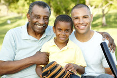 African American Grandfather, Father And Son Playing Baseball In Park royalty free stock images