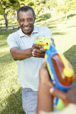 African American Grandfather And Grandson Playing With Water Pis Royalty Free Stock Photo