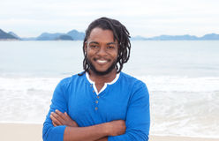 African american guy with dreadlocks and crossed arms at beach Royalty Free Stock Image