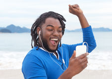 African american guy with dreadlocks listening to music at beach Stock Images