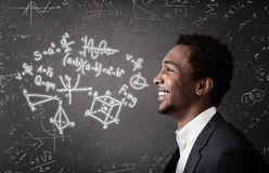 African American guy and formulas on chalkboard Royalty Free Stock Images