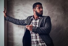 African-American guy holding a phone and turning around in a studio. royalty free stock images