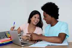 African american guy learning with caucasian female student. At desk at home Stock Images