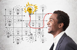 African American guy and shining light bulb in grid Royalty Free Stock Photos