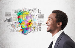 African American guy and startup and light bulb sketch. Smiling African American man standing near concrete wall with colorful light bulb and startup sketches Royalty Free Stock Image