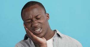 African american guy suffering from strong tooth pain