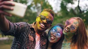 African American guy wearing sunglasses is taking selfie with female friends at Holi color holiday, their faces and hair. Are dirty with bright multicolor paint stock video