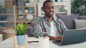 African American guy is working at home using laptop typing then making notes on paper and drinking sitting at desk at