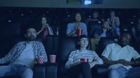 African American guy yawning in cinema disappointed with boring film. African American guy is yawning in cinema disappointed with boring film while people men stock video