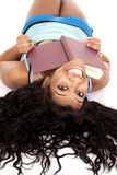 African American hair out book smile. An African American woman is laying upside down with a book and a smile Stock Photos