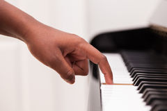 African American hand playing piano. Touching piano keys - Black people Stock Photos