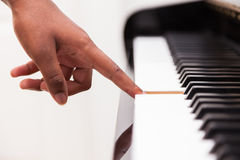 African American hand playing piano. Touching piano keys - Black people Stock Photography