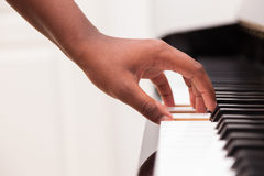 African American hand playing piano. Touching piano keys - Black people Stock Photo
