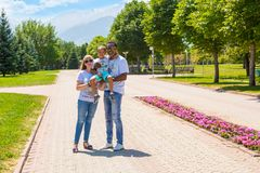 African American happy family: black father, mom and baby boy on nature. Use it for a child, parenting or love concept. African American happy family: black stock photography