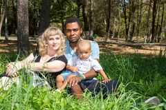 African American happy family: black father, mom and baby boy on nature. Royalty Free Stock Image