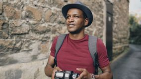 African happy tourist taking photo on his dslr camera. Young man travelling in Europe royalty free stock image