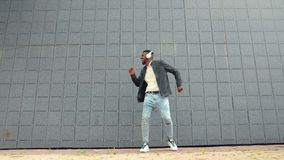 African American hipster in headphones dancing outdoors having fun. Slow motion portrait of African American hipster in wireless headphones dancing outdoors stock video