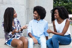 African american hipster man flirting with two woman. African american hipster men flirting with two women in the summer stock image