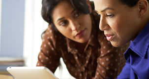African American and Hispanic business women using tablet computer Royalty Free Stock Image