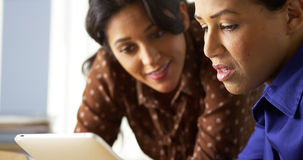 African American and Hispanic business women using tablet computer royalty free stock images