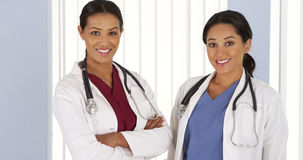 African American and Hispanic doctors smiling in hospital Royalty Free Stock Images
