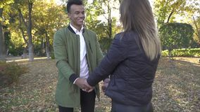 African American holds hands of his girlfriend in the park. Beautiful interracial couple chatting outdoors. Portrait of African American and Caucasian couple stock footage