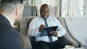 African american HR manager having job interview with young man in suit and watching his resume application in modern. Cafe indoors stock footage