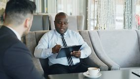 African american HR manager having job interview with young man in suit and watching his resume application in modern. Cafe indoors stock video
