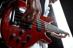 African American jazz musician playing bass guitar. African American handsome jazz musician playing bass guitar in the studio on a black background. Music royalty free stock photos