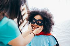 African American kid being supported and helped by supportive mother for little adventure and protection. African American kid being supported and helped by royalty free stock photos