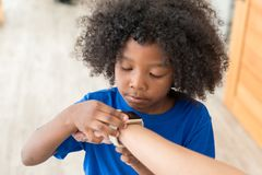 African American kid checking time on digital wristwatch stock photos
