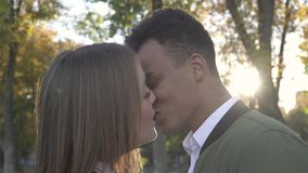 African American kisses his Caucasian girlfriend. African American guy with his Caucasian girlfriend. Portrait of African American and Caucasian couple in love stock video footage
