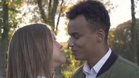 African American kisses his Caucasian girlfriend in the park. African American kisses his Caucasian girlfriend. African American guy with his Caucasian stock video footage