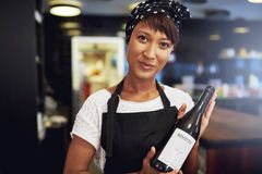 African American lady presenting a bottle of wine Royalty Free Stock Photography
