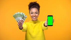 African-American lady showing smartphone and bunch of euros, money transfer. Stock photo royalty free stock images