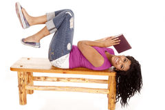 African American lay bench book. An African American woman is laying on a bench with a book Stock Images
