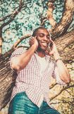 African american listens music in a park Stock Image