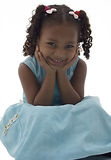 African American Little Girl in Blue Dress. An African American girl in a blue dress with her hands on her face and elbows in her lap Stock Photography