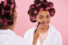 African American little girl doing makeup with mom. With hair curlers. Isolated on pink background stock photo