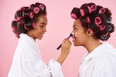 African American little girl doing makeup with mom. With hair curlers. Isolated on pink background royalty free stock photography