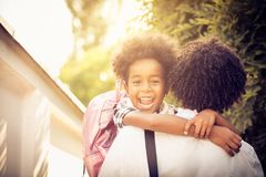 I go to school. African American little girl in fathers hug. Looking at camera. Close up stock photo