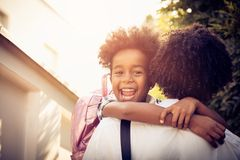 I go to school. African American little girl in fathers hug. Looking at camera. Close up royalty free stock images