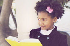African american little girl reading. Outdoors royalty free stock photos