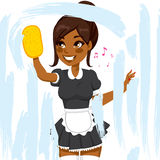 African American Maid Cleaning Window. Beautiful African American woman in maid dress working cleaning window with soap sponge Royalty Free Stock Images
