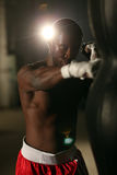 African American male boxer hitting punch bag in red shorts at the gym. African American male boxer hitting punch bag in red shorts in the gym Stock Images