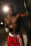 African American male boxer hitting punch bag in red shorts at the gym. African American male boxer hitting punch bag in red shorts in the gym Stock Image