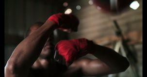 African American male boxer practicing boxing in fitness studio 4k. Front view of young African American male boxer practicing boxing in fitness studio. He is stock footage