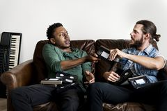 African American male and a Caucasian male hipsters fighting over VHS video tape stock photos